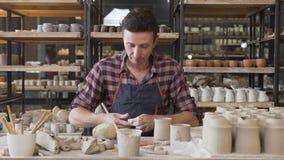 在瓦器的被聚焦的男性陶瓷工揉的黏土 影视素材
