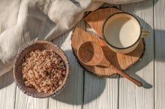 在瓦器碗、一个金属杯子用牛奶和一把木匙子的煮沸的荞麦谷物用一l装饰的土气木表面上 库存照片