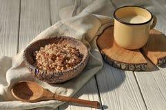 在瓦器碗、一个金属杯子用牛奶和一把木匙子的煮沸的荞麦谷物用锂装饰的土气木表面上 免版税库存图片