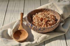 在瓦器碗和一把木匙子的煮沸的荞麦谷物用一张亚麻布餐巾装饰的土气木表面上 免版税库存图片