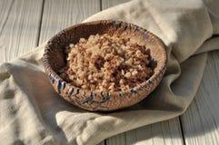 在瓦器碗的煮沸的荞麦谷物用一张亚麻布餐巾装饰的土气木表面上 免版税库存图片