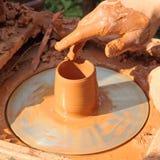 在瓦器轮子的陶瓷工手被采取的特写镜头 免版税库存照片
