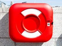 在瓦片墙壁上的红色救生衣 免版税库存照片