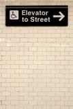 在瓦片墙壁上的纽约驻地地铁定向标志 免版税图库摄影