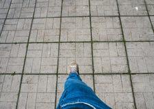 在瓦片的一个人的腿 免版税库存照片