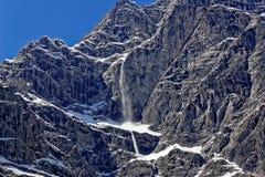 在瓦茨曼断层块的雪崩由蓝天 库存图片