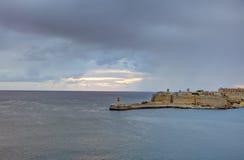 在瓦莱塔市的历史建筑的HDR视图,马耳他首都,有一座老红色和白色灯塔的,在surise期间 库存照片