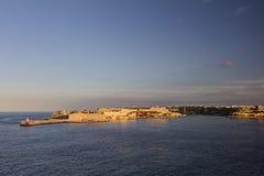 在瓦莱塔市的历史建筑的HDR视图,马耳他首都,有一座老红色和白色灯塔的 库存图片