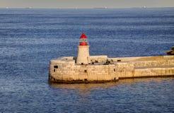 在瓦莱塔市的历史建筑的HDR视图,马耳他首都,有一座老红色和白色灯塔的 免版税库存图片