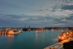 在瓦莱塔盛大港口的夜视图从在马耳他和堡垒St在另一边的安吉洛的历史的上部Barraka庭院区域 免版税库存图片