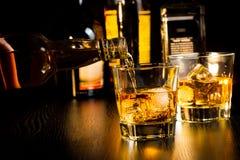 在瓶前面的男服务员倾吐的威士忌酒,在瓶顶部的焦点 免版税图库摄影