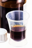 在瓶和塑料量杯的糖浆 库存照片