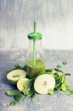 在瓶和成份的绿色圆滑的人:苹果和菠菜,在土气背景,正面图 库存图片
