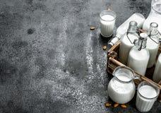 在瓶和水罐的新鲜的牛奶有一个木箱的 图库摄影