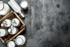 在瓶和水罐的新鲜的牛奶有一个木箱的 库存图片