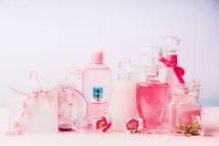 在瓶和瓶子的各种各样的自然化妆产品有在淡色背景,正面图的桃红色花的 秀丽和护肤骗局 库存图片