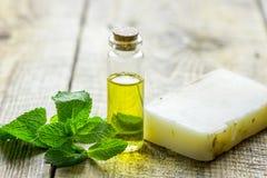 在瓶和肥皂的化妆油用在轻的桌背景的草本 库存照片