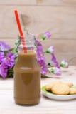 在瓶和黄油曲奇饼的热的咖啡在木头 库存照片