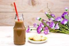 在瓶和黄油曲奇饼的热的咖啡在木头 免版税库存图片