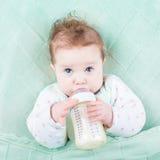 在瓶外面的逗人喜爱的小的婴孩饮用奶惯例 库存图片
