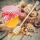 在瓶子、核桃在篮子和木浸染工的蜂蜜在老厨房 免版税库存照片