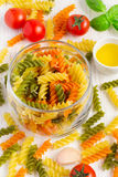 在瓶子、西红柿和spi的五颜六色的意大利fusilli面团 免版税库存照片