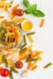 在瓶子、西红柿和spi的五颜六色的意大利fusilli面团 免版税图库摄影