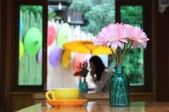 在瓶子和咖啡杯的美丽的花在与colo的木桌上 免版税库存照片