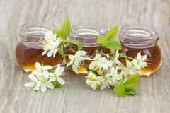 在瓶子和花的蜂蜜 免版税库存图片