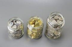 在瓶子的三不同大小-财政概念的硬币 免版税图库摄影