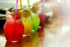 在瓶子的五颜六色的冷的意大利苏打糖浆服务 库存照片