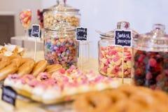 在瓶子的五颜六色的糖果在与油炸圈饼,曲奇饼的一张点心桌上 库存图片
