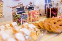 在瓶子的五颜六色的糖果在与油炸圈饼,曲奇饼的一张点心桌上 免版税库存图片
