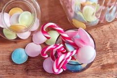 在瓶子的五颜六色的糖果在木背景的桌上 从存贮溢出的五颜六色的糖果刺激,老木背景 免版税图库摄影