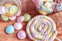 在瓶子的五颜六色的糖果在木背景的桌上 从存贮溢出的五颜六色的糖果刺激,老木背景 免版税库存图片