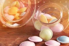 在瓶子的五颜六色的糖果在木背景的桌上 从存贮溢出的五颜六色的糖果刺激,老木背景 库存照片