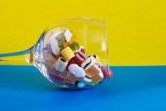 在瓶子的五颜六色的糖果在蓝色背景 图库摄影