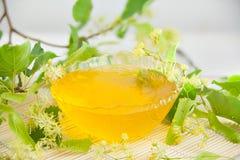 在瓶子的可口菩提树蜂蜜在桌上 图库摄影