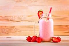 在瓶子的大,稀薄和平直的红色秸杆用饮料 一些个草莓在一个充分的瓶子草莓饮料附近 库存照片