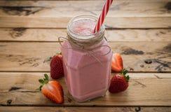 在瓶子的新鲜的草莓圆滑的人 背景空白木 Hea 免版税库存图片