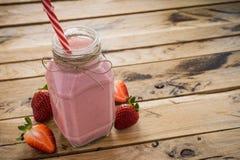 在瓶子的新鲜的草莓圆滑的人 背景空白木 Hea 库存图片