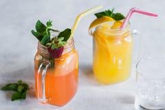 在瓶子的新鲜水果鸡尾酒在白色桌上 免版税库存照片