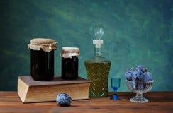 在瓶子的李子果酱玻璃、白兰地酒和新鲜水果 免版税库存照片