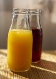 在瓶子的桔子和石榴汁抢劫 免版税图库摄影