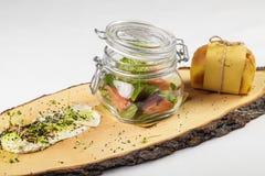 在瓶子的沙拉用调味汁和小小圆面包在木板在白色b 图库摄影