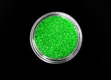 在瓶子的绿色发光的闪耀的眼影在黑背景 库存照片