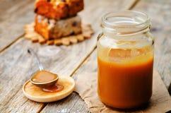 在瓶子的自创盐味的焦糖在黑暗的木背景 Th 库存照片