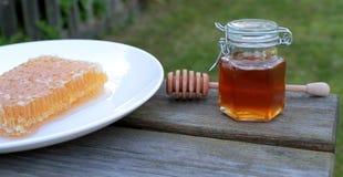 在瓶子的蜂窝和蜂蜜 免版税库存图片