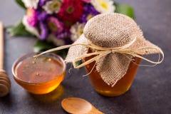 在瓶子的蜂蜜在厨房用桌上 图库摄影