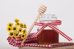 在瓶子的蜂蜜在木背景 免版税图库摄影